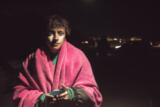 Jules from Philadelphia, Pennsylvania, recovers at the Mess Hall at Oceti Sakowin main camp after gathering at the barricade. White from milk of magnesia streaks her face as a result of being treated by Emergency medics for tear gas.